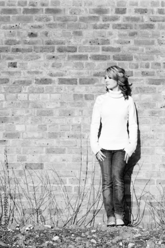 beautiful teen girl standing against  a derelict wall