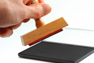 Hand mit Stempel vor Stempelkissen