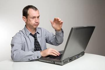 Homme devant ordinateur exprimant son ras le bol
