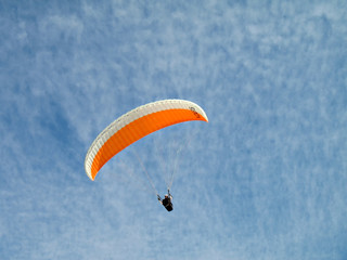 A paraglider il flying in the sky with his colourful paraglide