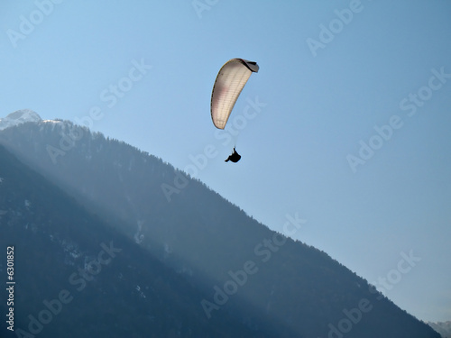 A paraglider il flying in the blue sky