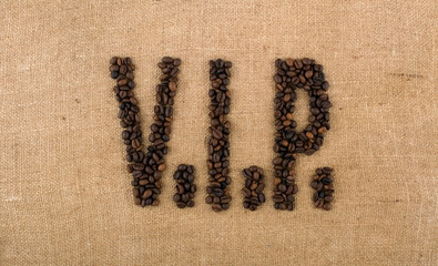 The word V.I.P. from coffee beans on linea material