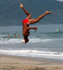 men doing capoeira on the beach