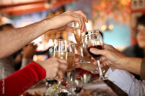 Leinwanddruck Bild Celebration. Glasses of champagne and wine in hands.