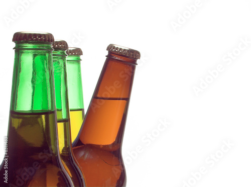 A delicious cold beer peeking from behind green bottles.