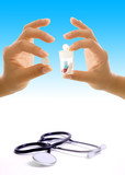 A stethoscope and two hands holding medications. poster