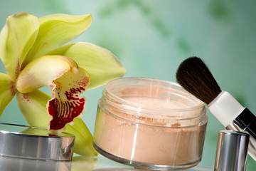 container of opened face powder, brush and orchid flower