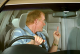 Middle aged man gives rude sign in road rage incident. poster