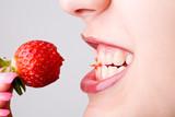 Fototapety Abgebissene Erdbeere zwischen Zähnen von Frau