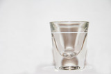 Shot Glass with white backround and slight reflection at base poster