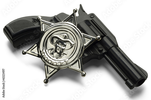 a toy gun with a sheriff's pin on white