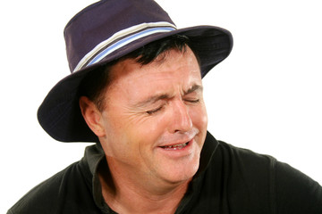 Middle aged man in a hat bursts into tears.