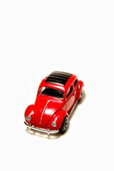 Red sedan matchbox toy car on white background.