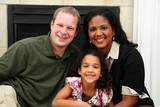 Interracial family sitting together at home poster