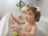 A child playing with soap foam in a bathtub. poster