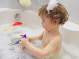 A child playing with toys in a bathtub. poster