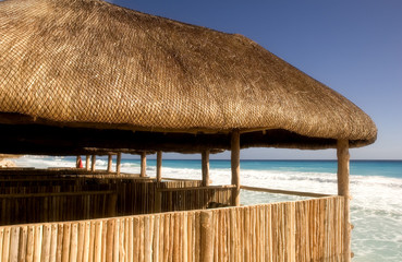 Straw and bamboo cabanas on the beach in front of a resort