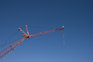 A red crane against a blue sky with a pulley attached