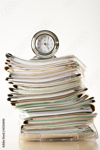 clock on a pile of files