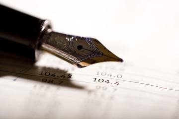an expensive pen on a financial magazine