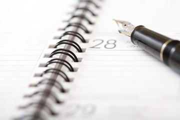 an expensive pen on an agenda 2