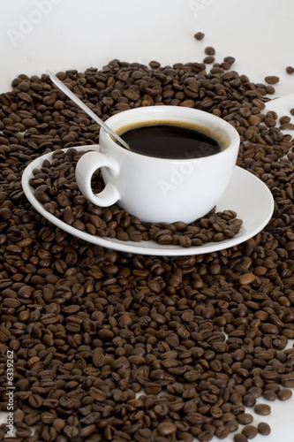 Cup of coffee view from above and coffee beans background