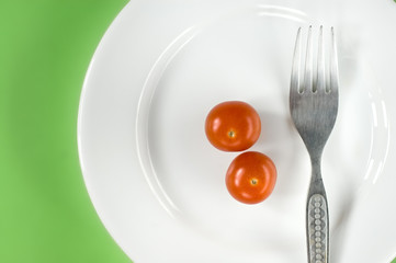 Two cherry tomatoes on a white plate with fork
