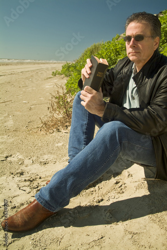 A man holding a bible, sitting at the edge of a sand dune.