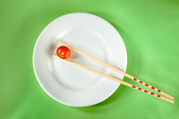 Cherry tomatoe on a white plate with chopsticks