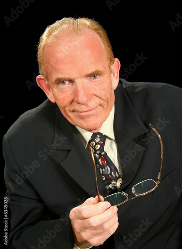 Middle aged businessman looking smug and holding glasses.