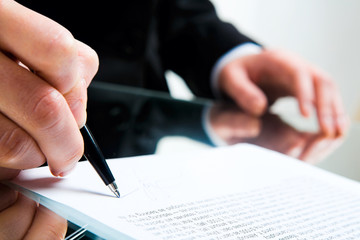 Closeup of business lady's hand with pen signing a contract