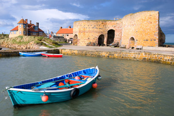 Rowing boat in Northumberland harbour overlooked by lime kilns
