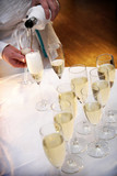 waiter pouring champagne for a toast to the bride and groom poster