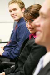 woman and two men looking at camera in boardroom meeting