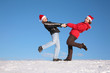 couple dance on  snow hill in santa claus hats 2
