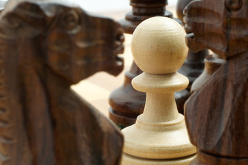 white pawn chessman surrounded by black pieces