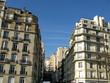 Rue parisienne ensoleillée avec façades blanches.