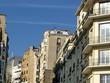 Rue parisienne avec immeubles anciens et modernes.