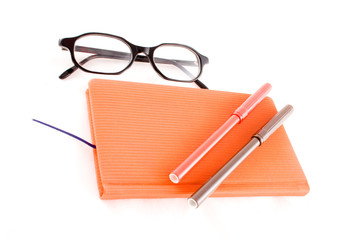 red book, black glasses and markers