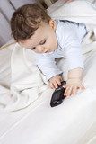 The little boy of 7 months plays with a cellular telephone  poster
