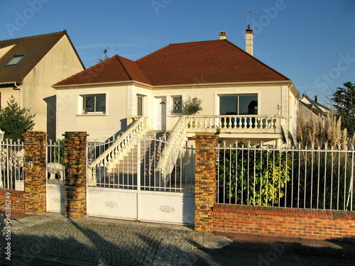 maison de banlieue blanche au toit rouge avec grille photo libre de droits sur la banque d. Black Bedroom Furniture Sets. Home Design Ideas