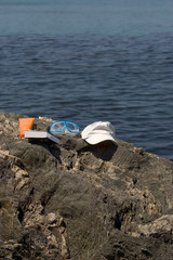 Objects of bath with a book posed at the edge of sea.