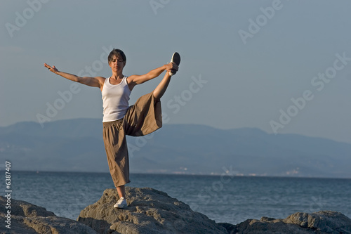 Woman making a exercise of balance at the seaside