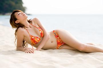 relaxing woman sun bathing by the beach