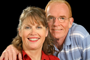 Happy middle aged couple smiling and looking to camera.