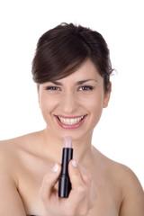 Woman doing makeup close up, focus on the face