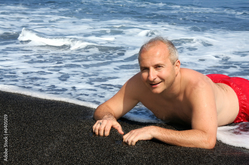 Mature man on a black sand beach on Big Island, Hawaii