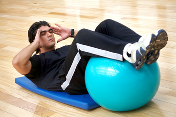 man at the gym doing abs exercises with a pilates ball