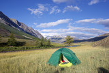 tent near the river and remote mountain peaks