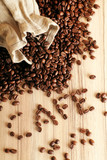 Fototapety some coffee beans and a jute sack with the word cafe